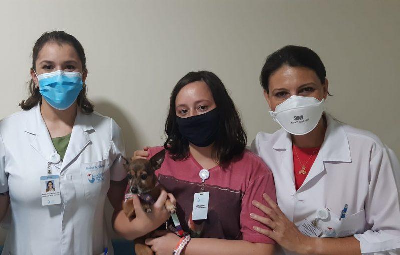 Lilica foi visitar o seu tutor acompanhada de uma familiar e foi recepcionada pela enfermeira Rafaella (esquerda) e a psicóloga Maria José (direita) – Foto: Hospital Dona Helena/Divulgação