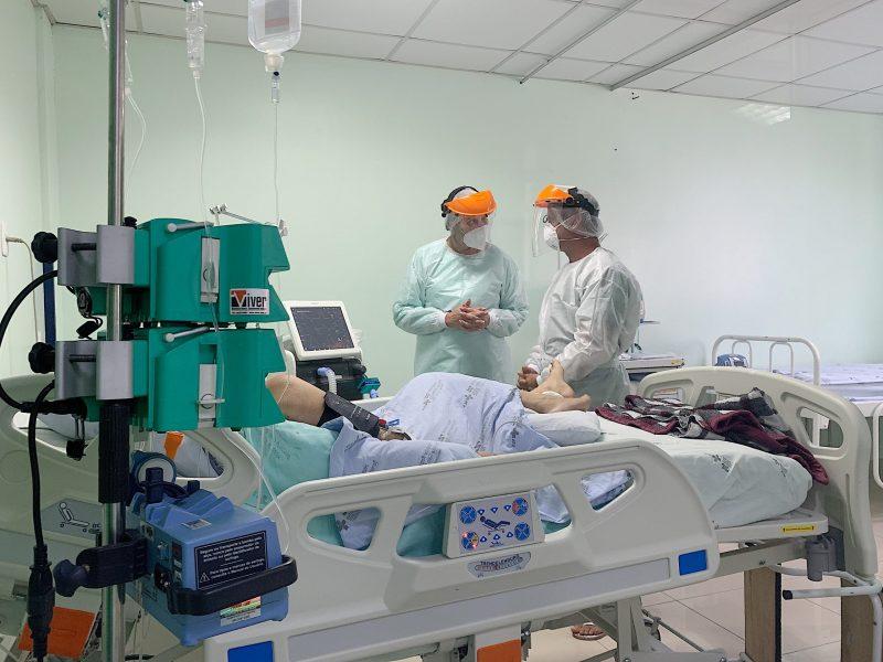 Leito de UTI com paciente e médicos ao redor