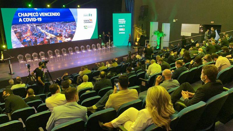 Em um auditório, o presidente em conjunto com outras autoridades políticas, discursaram sobre a melhora de Chapecó, em relação a pandemia. – Foto: William Ricardo/ND