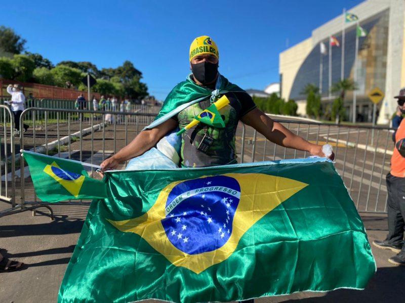 """Tiago, de São Paulo. """"Eu estou aqui porque gosto dele. Estou trabalhando na cidade e sou apoiador"""", disse. O jovem é um dos apoiadores do presidente que se aglomeram na frente do Centro de Eventos. – Foto: William Ricardo/ND"""