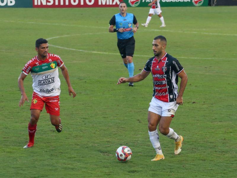 Davi Lopes, vesito com o primeiro uniforme, domina bola e marcado por jogador do Brusque; Arbitro aparece no fundo acompanhando a jogada