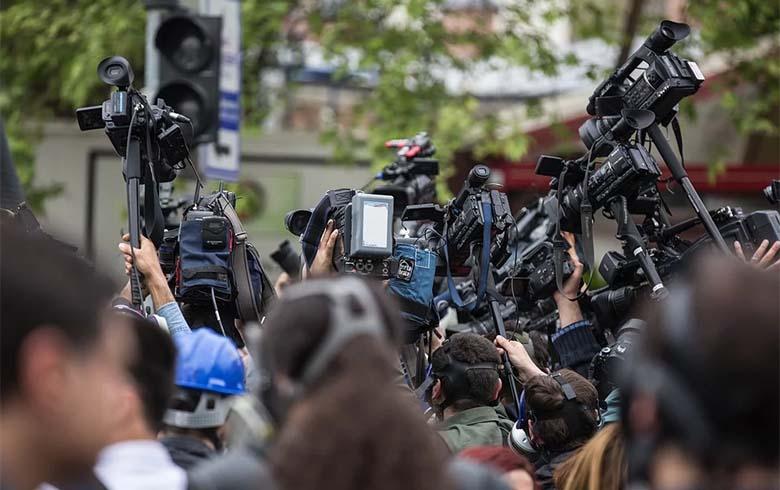 Câmeras e jornalistas em uma rua