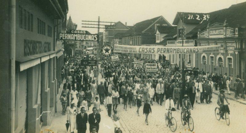 A rua XV de Novembro foi o palco de momentos históricos, como o protesto dos integralistas, Movimento Blumenau Unido, desfiles de Carnaval, das misses Vera Fischer e Ingrid Budag, dos desfiles anuais de aniversário da cidade. Também fazem parte da história da via os desfiles da Oktoberfest, que iniciaram em 1984, a recepção de personalidades como Helmuth Kohl, Getúlio Vargas, Ernesto Geisel e Castelo Branco, que desfilaram e discursaram na importante rua do Centro. Na imagem de 1934, o Movimento Blumenau Unido mobilizou os moradores da cidade em protesto contra o interventor estadual Coronel Aristiliano Ramos, devido a criação do decreto que desmembrava os distritos de Blumenau, criando os municípios de Indaial, Gaspar, Timbó e Dalbérgia (Ibirama). Com esta legislação, o território blumenauense foi violentamente reduzido. Na imagem, o Movimento Blumenau Unido em protesto na Rua XV. – Fonte e foto: Fundação Cultural de Blumenau / Arquivo Histórico José Ferreira da Silva