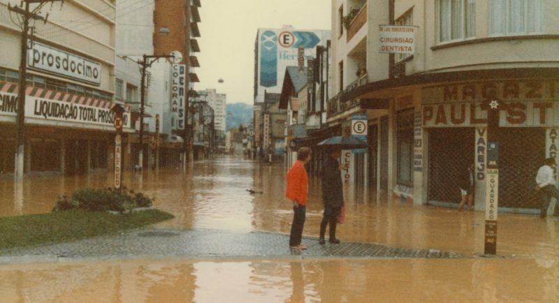 A principal rua da cidade foi importante desde o seu início até os dias atuais e tem sido palco de diversas manifestações, nos momentos de alegria e de tristezas como as enchentes de 1911, 1983 e 1984 que deixaram suas marcas. Houve também incêndios que consumiram importantes prédios, como a antiga sede da Prefeitura (1958), onde hoje está a Fundação Cultural de Blumenau, a Casa Caça e Pesca (1986) e o Edifício Catarinense (1996). Na imagem destaca a Rua XV sendo invadida pelas águas na enchente de 1984. – Fonte e foto: Fundação Cultural de Blumenau / Arquivo Histórico José Ferreira da Silva