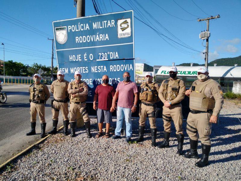Policiais rodoviários em frente à placa que mostra o número de mortes no trecho – Foto: Divulgação/ND