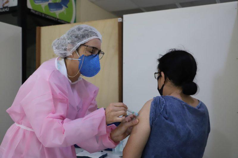 enfermeira aplicando vacina em idosa