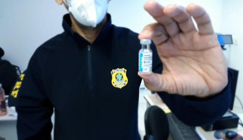 Policial segurando a vacina