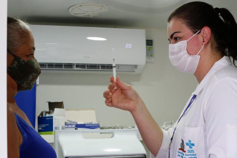 Enfermeira mostra dose da vacina para mulher