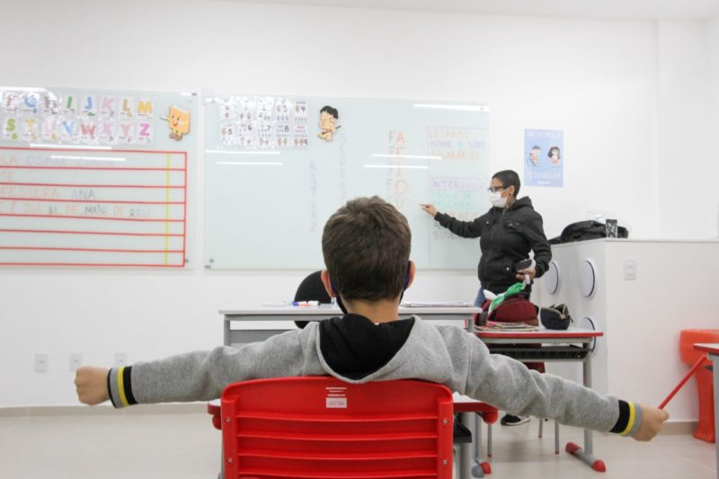 Aluno de braços abertos e sentado em cadeira vermelha e professor no fundo com máscara