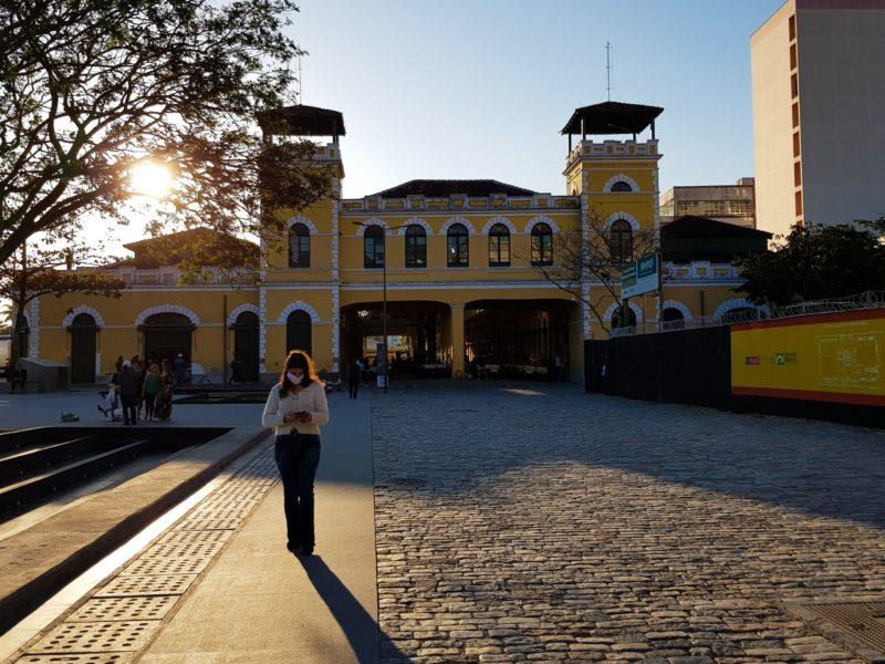 Imagem mostra mulher de cabeça baixa e no fundo o Mercado Público de Florianópolis o tempo está ensolarado