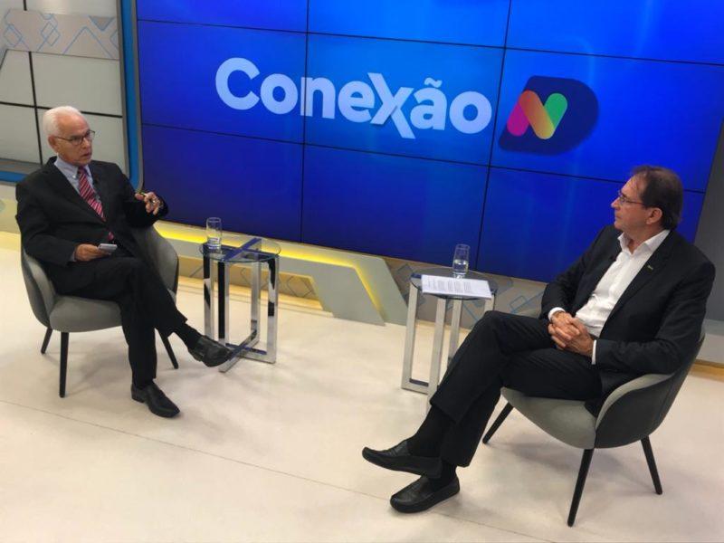Moacir Pereira aparece conversando com presidente da Fiesc e telão na parte central escrito Conexão ND com o fundo azul