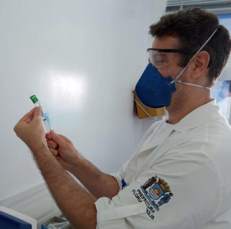 enfermeiro colocando insumo da vacina na seringa