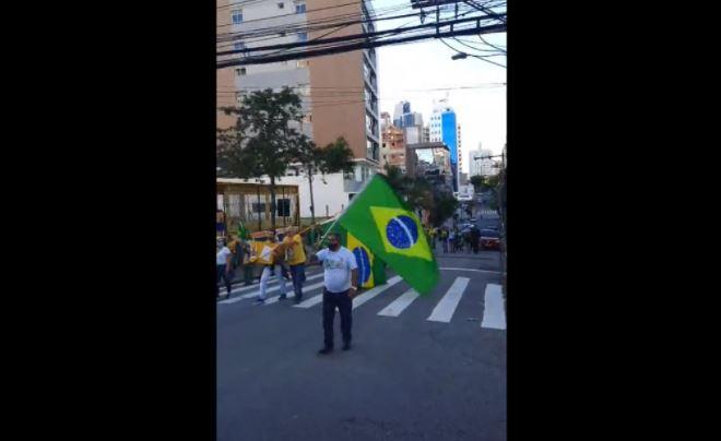 Imagem mostra homem segurando bandeira do Brasil