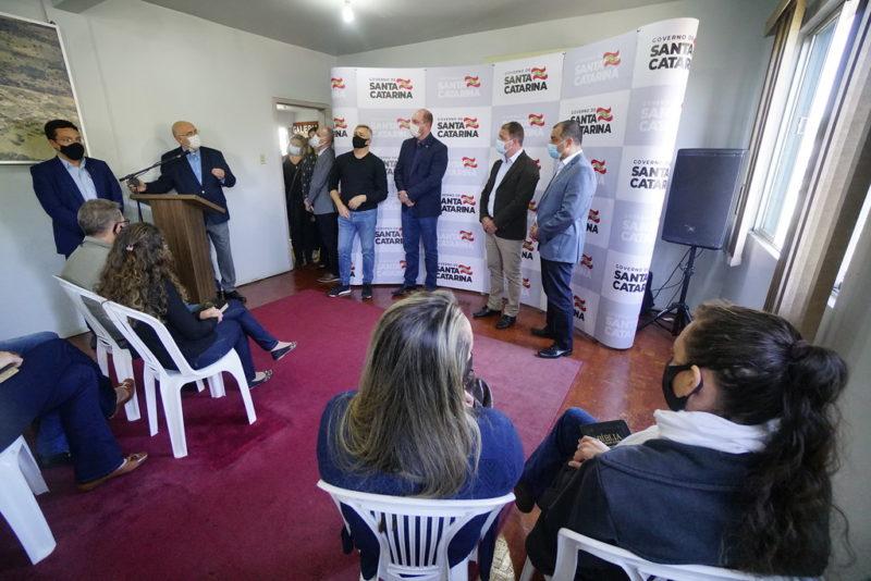 Imagem mostra pessoas em uma sala com tapete vermelho e banner do Governo de Santa Catarina