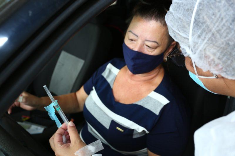 enfermeira mostrando a vacina para mulher do grupo prioritário