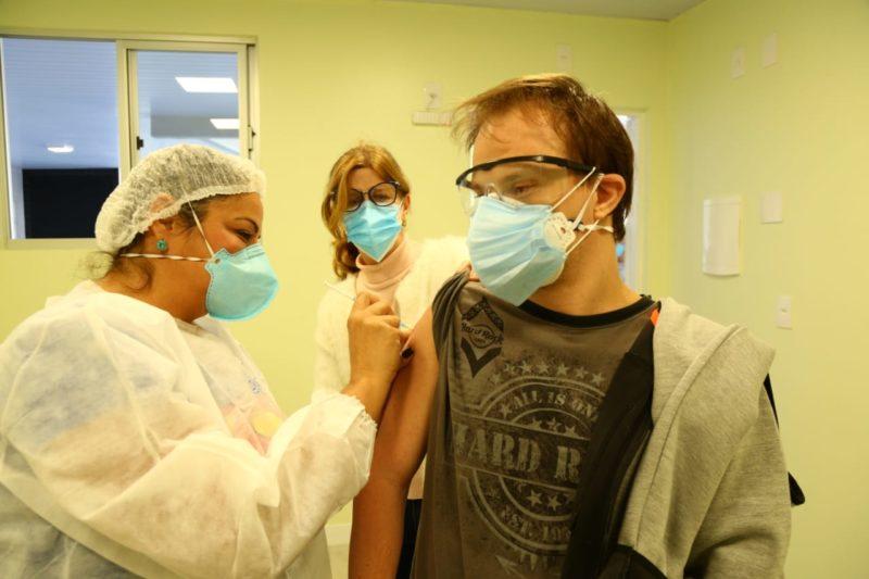 pessoa com sindrome de down recebendo a vacina