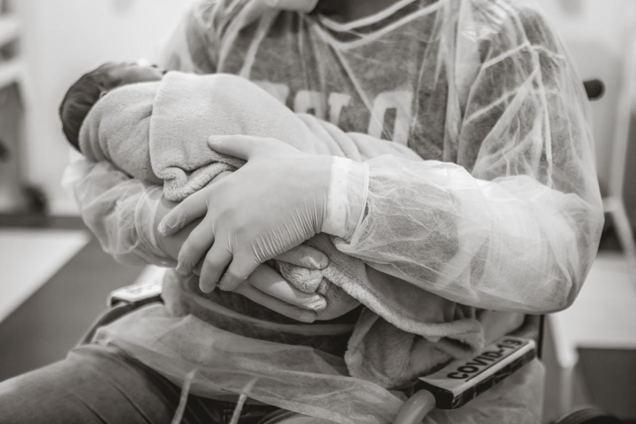 Pai conseguiu pegar o filho no colo brevemente após o parto, com luvas e máscara - Bruna Costa