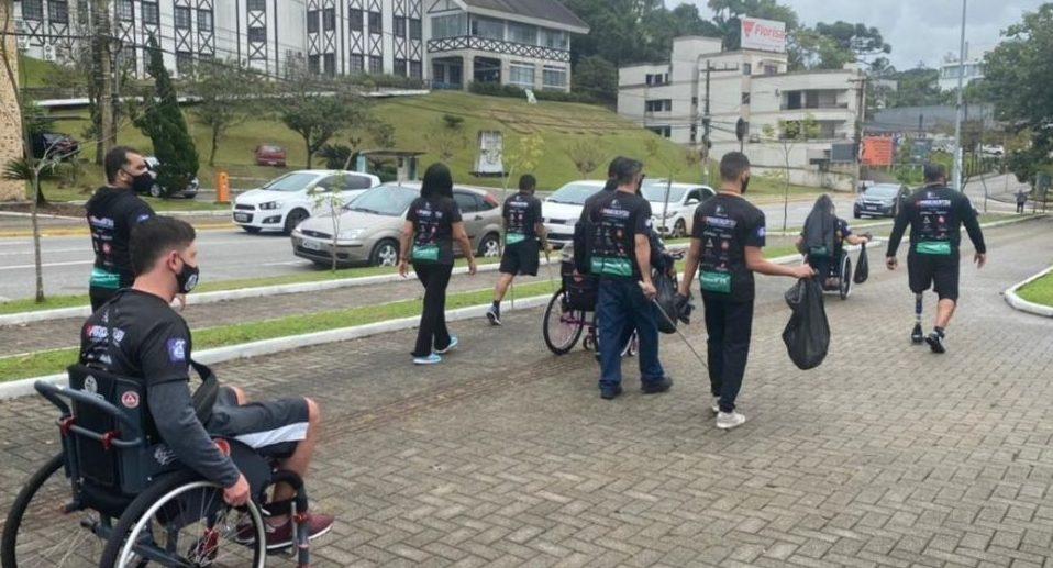 Colegas de paratleta que pichou ponte em SC se desculpam limpando praça - Divulgação