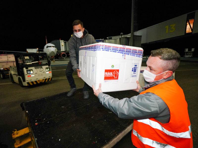 Homens segurando uma caixa de isopor no aeroporto