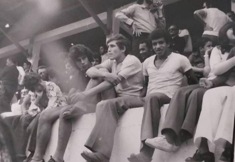 Na foto do início da década de 1970, o atacante Tião Marino aparece sentado entre os meias Caco e Luiz Everton (camisa escura) em um momento de pura descontração nas arquibancadas entre os torcedores, aqui na capital. Esse trio deu muitas alegrias para os torcedores do Figueirense. Luiz Everton e Caco, depois mais tarde, vestiram a camisa do Avaí. – Foto: Tião Marino/Jorge Custódio/mídia social/ND