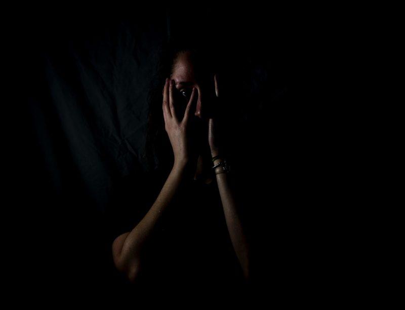 Mulher com mão no rosto e fundo preto