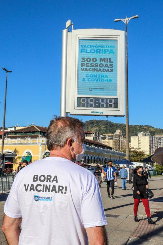 Prefeito Gean Loureiro em frente ao Ticen, próximo a um relógio que registra marca conquistada pela campanha de imunização contra a Covid-19 – Foto: Divulgação/PMF/ND