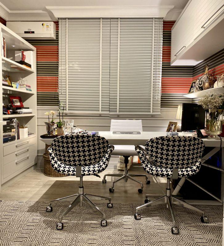 A base do espaço em tons claros acolhe o papel de parede com listras horizontais, em cores mais quentes. As cadeiras com tecido no estilo Pied de poule também se destacam – Foto: Divulgação Cláudia Couto