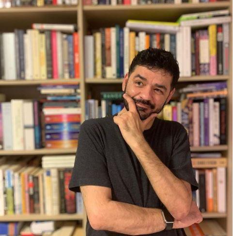 Magro Lima com camisa preta e no fundo é possível ver estante com livros