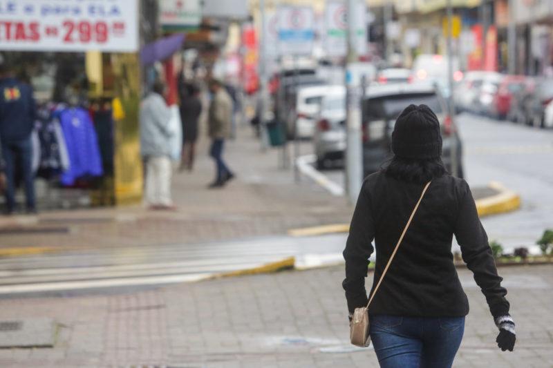 mulher de casaco atravessa a rua em joinville