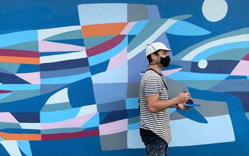 """Pintando o mural """"Família de Golfinhos Felizes no Encontro"""" (2021), na avenida Campeche, em Florianópolis – Foto: Anna Rezende/Divulgação/ND"""