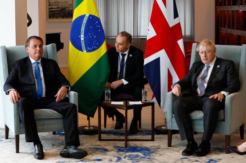 Imagem mostra Presidente Bolsonaro na esquerda, ao lado da bandeira do Brasil, no meio o traduro, ao lado a bandeira do Reino Unido e o primeiro-ministro Boris Johnson. Todos estão com terno preto