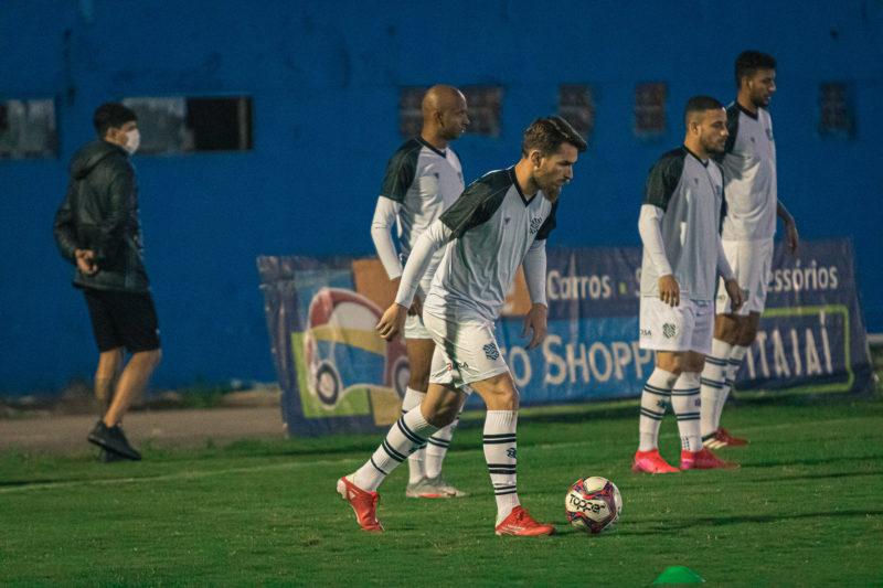 Imagem mostra jogadores do Figueirense usando uniforme branco e Krobel com a bola próximo do pé direito