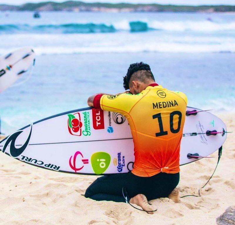 surfista Gabriel Medina ajoelhado com uma prancha