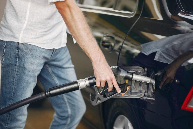 Imagem mostra homem usando camisa branca e abastecendo um veículo da cor preta